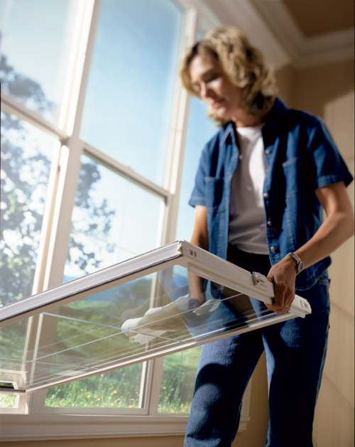 woman cleans single and double hung window with tilt feature - easy cleaning